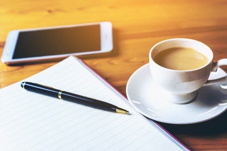 on wooden table in  coffee shop interior near mobile phone and cup of  coffee book pen and smartphone Stock Photo