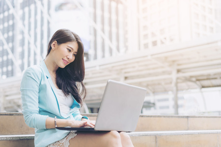 Beautiful cute girl smiling in business woman clothes  using laptop computer  , urban city background Stock Photo