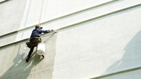 painter hanging on white building Stock Photo