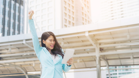 lifestyle business woman feel happy  to raise while using   tablet phone smartphone , business concept Stock Photo