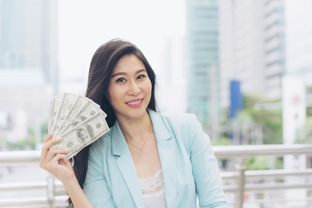 Successful beautiful  asian business  young woman holding money US dollar bills in hand , business concept Stock Photo