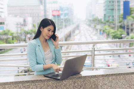 Beautiful cute girl smiling in business woman clothes  using laptop computer and smartphone , urban city background Stock Photo