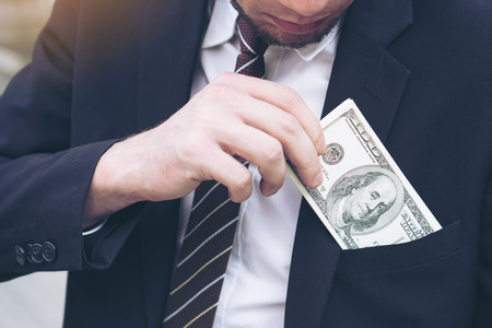 business man Picking up money US dollar bills sticking out of his pocket , concept for success business
