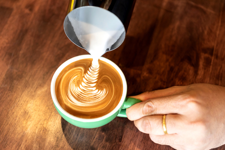 Closeup image of male hands barista pouring milk  make  coffee latte art in coffee shop cafe Stock Photo