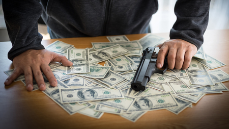 businessman stressed from work at office desk holding a gun
