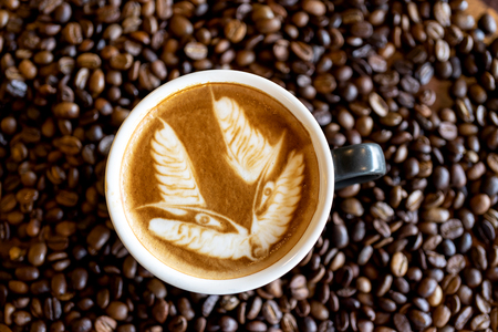 Hot art coffee latte art in a cup on coffee bean background Stock Photo