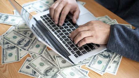 top view business people working with laptop hand typing on keyboard computer for business , us dollar bill  on office desk Stock Photo