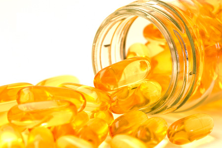 Fish oil, omega 3 with vitamin D capsules good for heart health on a white backguound, healthy diet concept Stok Fotoğraf