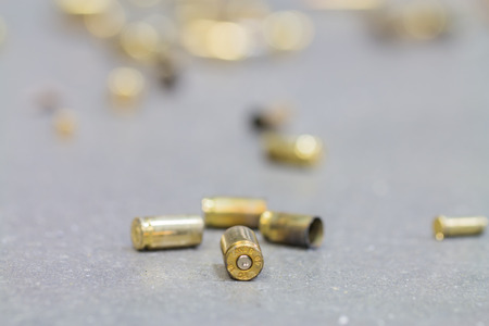 Spent shell casings on cement background.