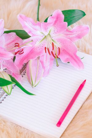 lilies and pen on notebook with fur rug background.