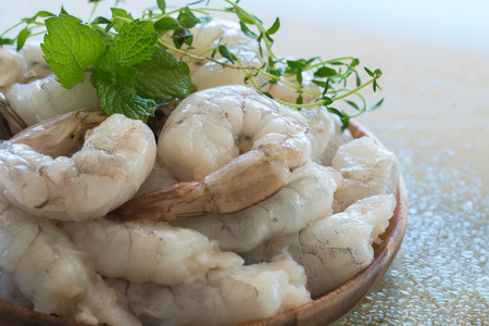 Raw shrimps in wooden plate. Stock Photo