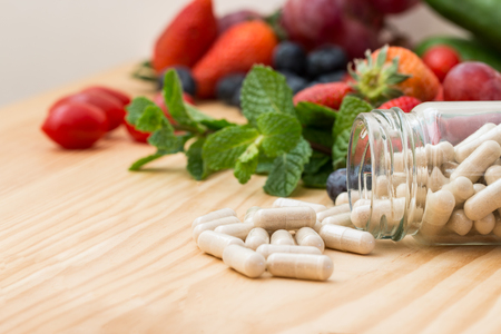 Vitamins supplements in bottle on wooden table.