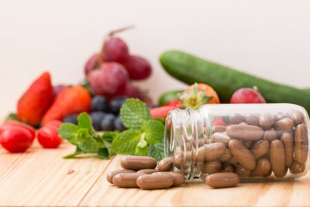 Vitamins supplements in the buttle and wooden table. Banco de Imagens