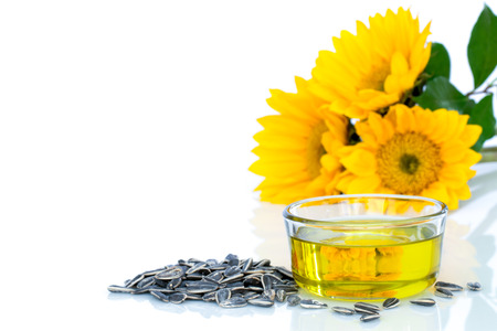 Sunflower, oil and seeds on white background.