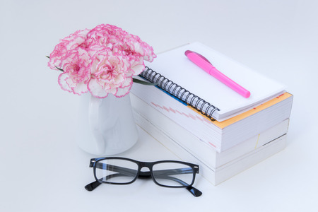 notebook, book, pen with glasses and carnation flowers on wooden table,  top view. Stock Photo