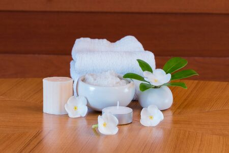Spa salt with nature soap bath on wooden table.