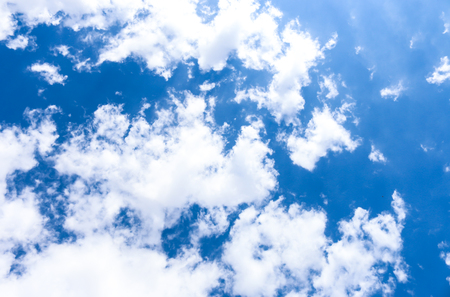 White clouds and sun on blue sky background