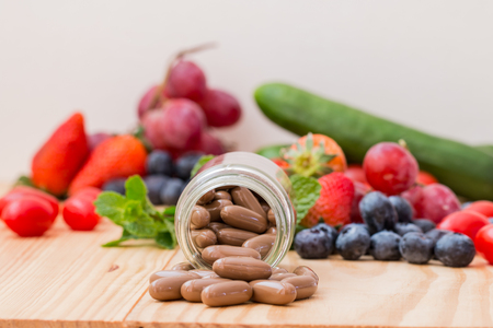 brown supplements in bottle on wooden table.