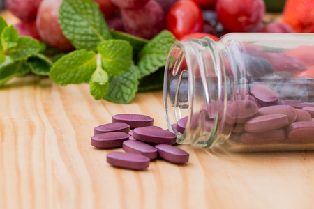 Purple supplements on wooden table.