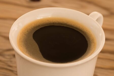 Cup of coffee on wooden table, close up.