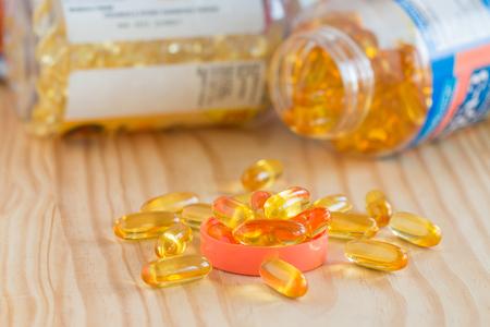 Aceite de pescado, omega 3 con cápsulas de vitamina D bueno para la salud del corazón en la mesa de madera y en botella. Foto de archivo - 83078560