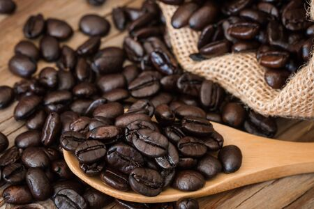 sackcloth: Roasted coffee beans in a sack and in the spoon on old wooden background. Stock Photo