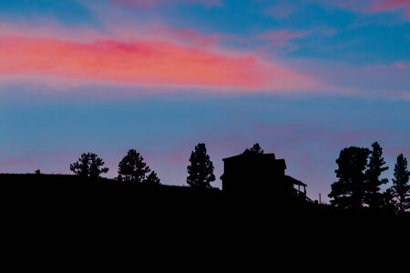 Beautiful sunset behind pine tree and house. Stock Photo