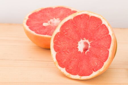 Half of organic grapefruit on wooden background.