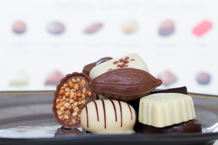 Assorted gourmet chocolate candies in different shapes and colors in the dish.