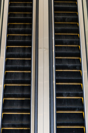 go up: Escalators go up and down in a building. Stock Photo