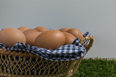 egg: Basket contains group of chicken eggs put on grass.