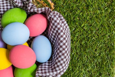 huevo: Grupo de los huevos de colores en una cesta colocada en campo de hierba verde.