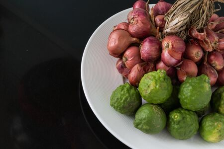 shallot: Raw bergamot and shallot in a plate on black background