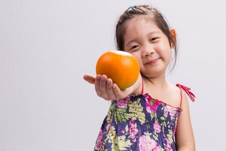 naranja fruta: Ni�o con la naranja. Ni�o con fondo naranja Foto de archivo