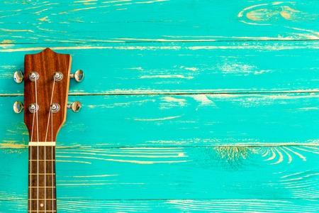 青い木製の背景にウクレレ 写真素材
