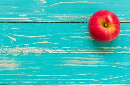 ヴィンテージの木製の背景の上のリンゴ