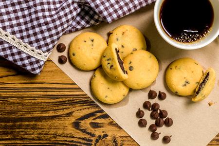 chocolate cookie: Galleta de chocolate con café sobre fondo de madera Foto de archivo