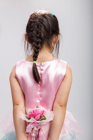 girl holding flower: Little Girl Holding Flower, Rear View Stock Photo