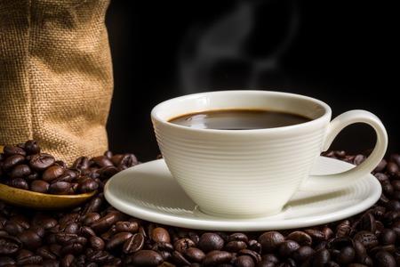 taza: Taza de caf� y frijoles en el fondo Negro Foto de archivo