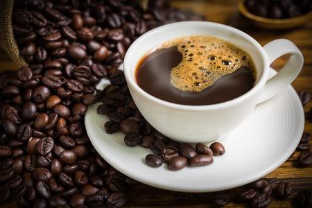 taza de café: Taza de café y frijoles en la mesa de madera