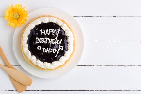 白い木製の背景にお誕生日おめでとうケーキ 写真素材