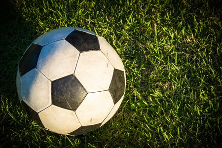 ballon foot: Old Ball in Grass Field Banque d'images