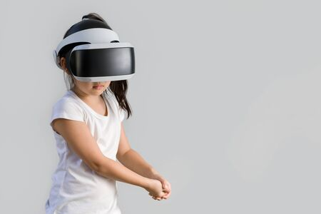 virtual world: Kid with Virtual Reality, VR, Headset Studio Shot Isolated on White Background. Child Exploring Digital Virtual World with VR Goggles. Stock Photo