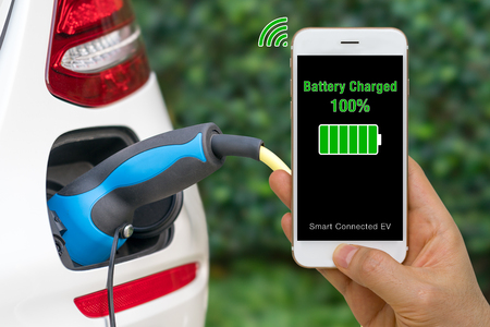 Connected Car Concept Illustrated by Smartphone App Showing Status of Battery Charged into Electric Vehicle