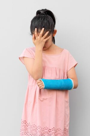 Asian Child with Broken Arm in Cast with Hurting and Sad Face Expression