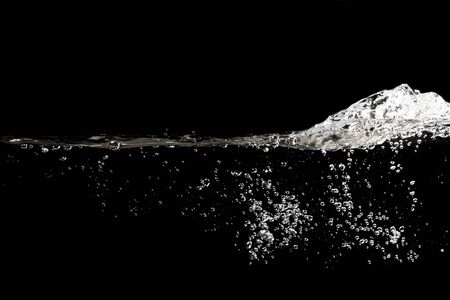 Nahaufnahme von Wasserwellen spritzen und Blasen auf schwarzem Hintergrund isoliert.