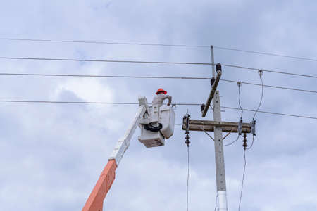 electrician works on cable car to maintain high voltage transmission lines.