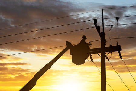 silhouette electrician works on cable car to maintain high voltage transmission lines.