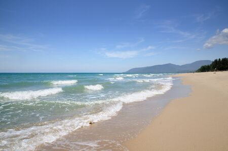 Turquoise tropical sea surf, wave foam, blue sky on empty sandy beach, Na Dan Beach in Nakhon Si Thammarat province of Thailand. Reklamní fotografie