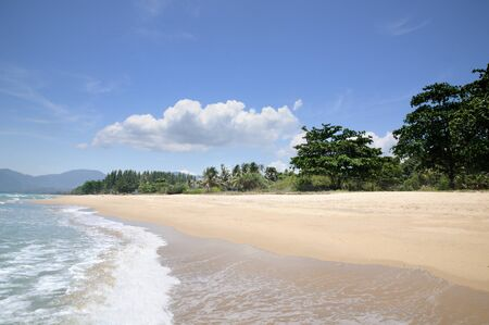 Turquoise tropical sea surf, wave foam, blue sky on empty sandy beach, Na Dan Beach in Nakhon Si Thammarat province of Thailand.